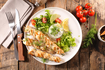 grilled chicken skewer with salad and sauce