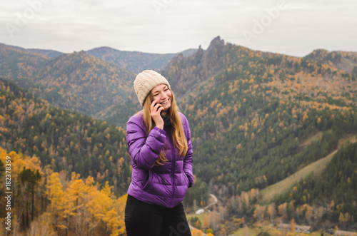 Plexiglas Khaki A girl in a lilac jacket talking on the phone in the mountains, an autumn forest with a cloudy day, free space for text