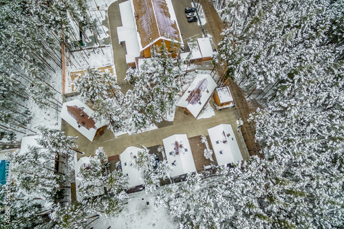 Wooden house in the middle of a winter forest. Aerial view snowy landscape. shooting from a drone