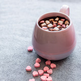hot chocolate  pink ceramic mug marshmallows and heart shaped pink chocolate candies  gray knitted background - 182387196