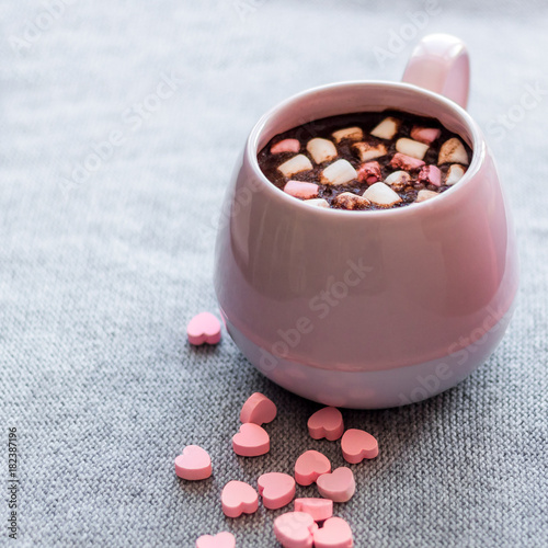 hot chocolate pink ceramic mug marshmallows and heart shaped pink chocolate candies gray knitted background