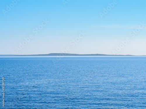 Poster Oceanië Rippled Water Of The Sea And Island Ahead Seascape