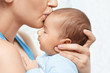 mother holding and kissing newborn baby