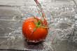 Wasser über die Tomate giessen