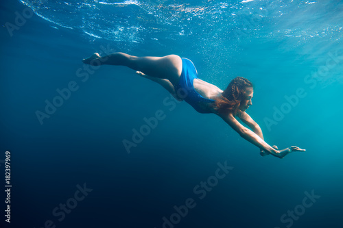 Young woman in bikini swimming in ocean