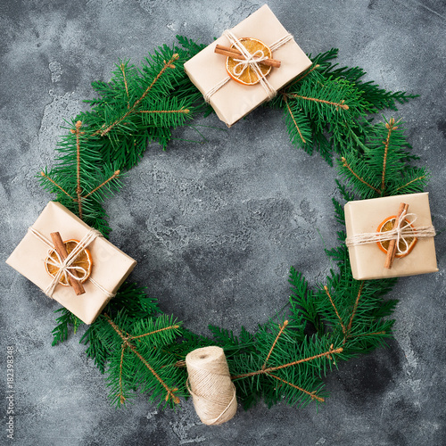 Round frame made of fir branches and craft gift box on dark background. Christmas, New year composition. Flat lay. Top view