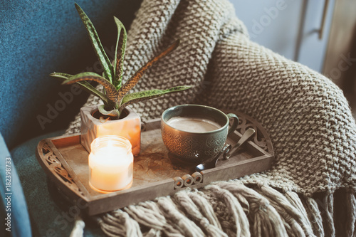 cozy winter morning at home. Hot cocoa or coffee with candle on blue nordic style chair