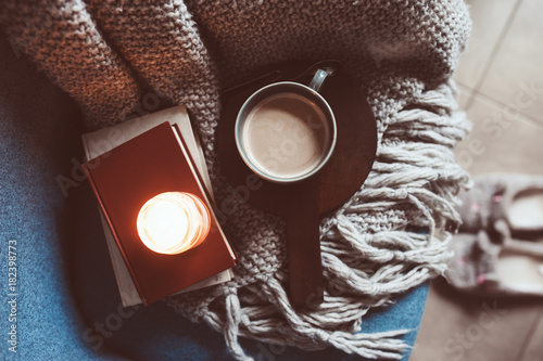 Cozy winter weekend at home. Morning with coffee or cocoa, books, warm knitted blanket and nordic style chair. Hygge concept.
