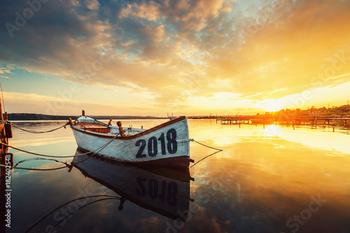 Foto auf Acrylglas See sonnenuntergang Happy New Year 2018 concept, lettering on the Boat with a reflection in the water at sunset