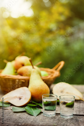 Plakat Shot glass with fruit brandy and pear