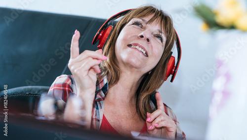 Fotobehang Muziek Happy mature woman listening to music