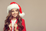 Portrait of cute smiling woman in santa hat. Christmas. - 182406302