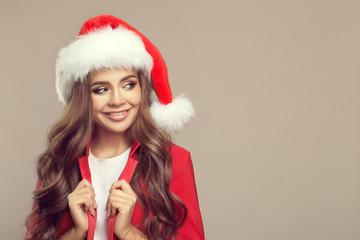 Portrait of cute smiling woman in santa hat. Christmas.
