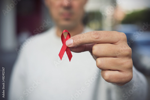 man with red ribbon for the fight against AIDS