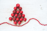 red Christmas baubles in the shape of a fir tree on white painted rustic wood, christmas background or greeting card, flat top view from above, copy space - 182422782