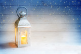 Christmas background with a lantern and burning candle light on rustic white wood, blue sky with stars, copy space - 182423102