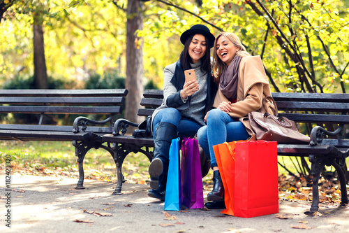 Two smiling young woman with shopping bag sitting on bench in park Poster
