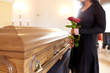 Quadro woman with red roses and coffin at funeral