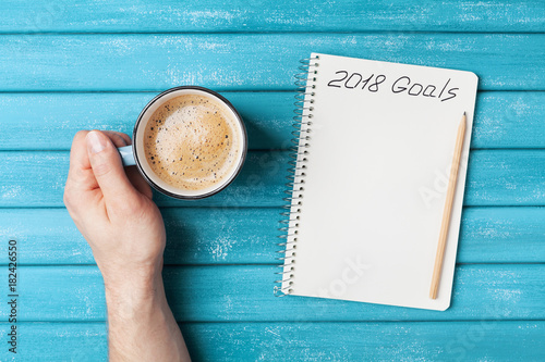 Notebook with text 2018 goals and cup of coffee on wooden desk top view. Planning and business concept. New year resolution.