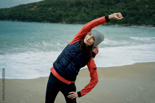 Staande foto Jogging Young woman wearing a sports vest exercising by winter sea