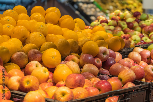 Fruit department in the supermarket. Oranges and apples