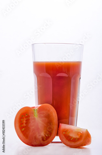 Poster Sap glass with tomato juice and sliced tomato on white background