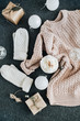 Feminine winter clothes look on grey plaid. Warm beige sweater and white knitted mittens, gift box and glass balls. Christmas fashion composition. Flat lay, top view.