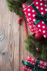spruce branches and red boxes with gifts on a wooden background
