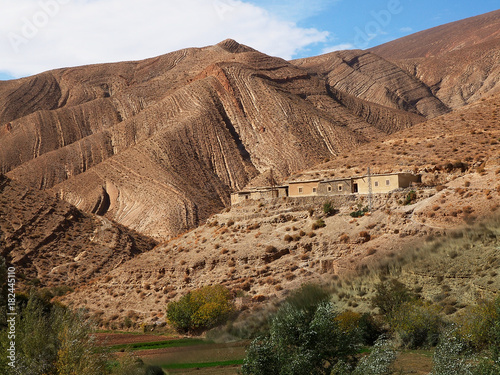 Staande foto Marokko Tiny moroccan village lost in the red canyons of the Gorge du dades valley in the north Africa / Morocco. Stripes pattern on the of the brown soil