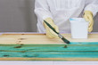 Una persona da color a una madera con una brocha y tinte azul