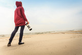 Woman walking on beach with camera - 182452376