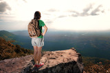 Young woman with backpack standing on cliff's edge at high mount