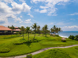 Golf club with green hills and many palm trees near Tanah lot temple, Bali island, Indonesia.