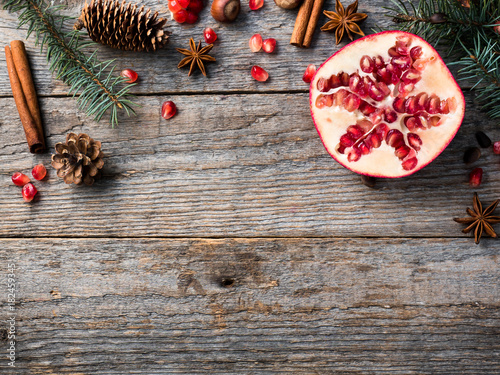 Pomegranate spruce branches star anise nuts, cinnamon and winter spices on wooden background, Rustic style Copy space