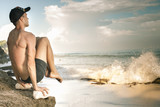 Handsome man doing yoga at cliff with blue sea background - 182460510