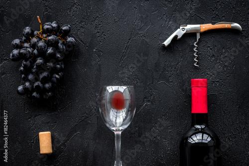 Open wine bottle. Grape, glass and corkscrew on black background top view