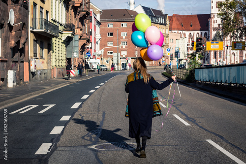 woman walking in the city with colorful helium balloons Poster