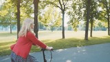 Active fashionable blonde woman riding a bike in the park at sunset. Good day for a ride - 182467504