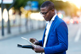 Handsome young business man using his digital tablet in the street. - 182469388