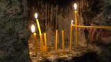 Beautiful girl kindles candle in old monastery - 182476122