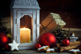 Christmas scene with lantern and a burning candle, gifts in kraft paper, red christmas ornaments, pine cones and cinnamon star cookies on a rustic wooden background - 182479995