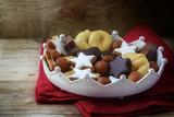 Christmas cookies and sweets like homemade cinnamon stars, marzipan balls, chocolate and biscuit in a pottery crown bowl on a red napkin, rustic wooden background, copy space - 182480330