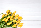 Bouquet of yellow tulips on white wooden background. Top view, copy space