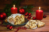 festive christmas cake, german criststollen with raisins and almonds, decorated with burning candles, red christmas balls and fir branches on a rustic wooden background - 182481732