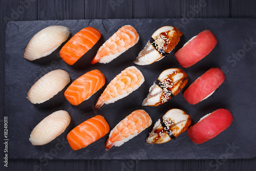 Staande foto Sushi bar Nigiri sushi set on black stone slate, flat lay. Delicious traditional Japanese food, tasty seafood, sushi restaurant concept