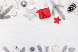christmas tree decorations and gingerbread cookies with red gift box on white wooden background flat view