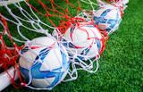Three Soccer footballs in training goal net for sport concept