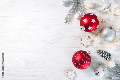 Foto Murales christmas glass balls with gingerbread cookies and garland on white wooden background flat view