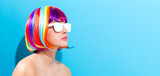 Beautiful woman in a colorful wig on a blue background - 182501768
