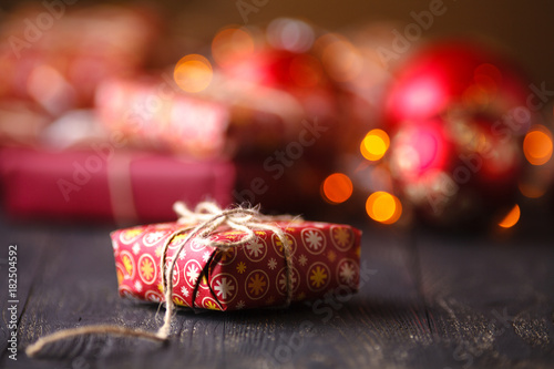 one christmas gift box in front of a bunch of presents on the table Poster